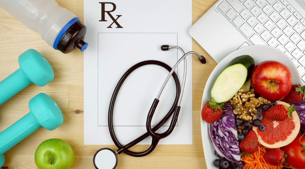 Image of hand weights, water bottle, fruit, stethoscope and laptop